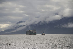 Barca rebocada pelo rebocador em nuvens litorais de Alaska e no fundo montanhoso Fotografia de Stock