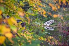 Barca a remi di pesca parcheggiata lungo la riva del lago Fotografie Stock Libere da Diritti