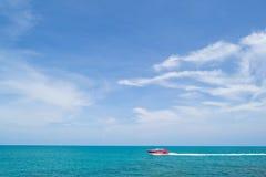 Barca rossa che si muove nel mare blu Immagine Stock