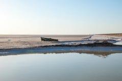 Barca rotta sulla riva di un lago di sale Immagine Stock