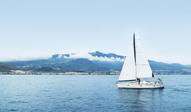 Barca saling bianca in mare vicino alla costa montainous fotografia stock libera da diritti
