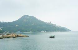Barca sola nel mare e nella montagna Fotografie Stock
