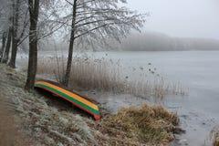 Barca sola sull'inverno congelato della riva del lago Immagine Stock