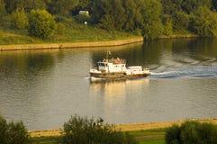 Barca su un fiume in città Fotografia Stock