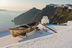 Barca su un tetto della casa al tramonto davanti alla roccia di Skaros al villaggio di Imerovigli, isola di Santorini Fotografia Stock Libera da Diritti