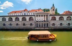 Barca sul fiume di Ljubljanica e sulla chiesa di San Nicola nel backgro Immagini Stock Libere da Diritti