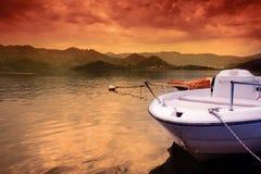 Barca sul lago e sul cielo variopinto di tramonto fotografia stock libera da diritti
