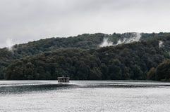 Barca sull'acqua con una foresta Fotografie Stock