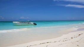 Barca sulla riva di un'isola tropicale con la sabbia bianca lavata dal mare azzurrato stock footage