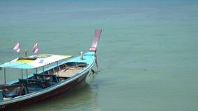 Barca tailandese del longtail che passa i turisti di attesa nel mare sulla spiaggia tropicale, fuori dalla costa di Phuket Tailan video d archivio