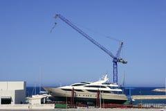 Barca tirata con la gru su area di memoria Immagini Stock