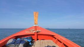 Barca tradizionale a sud della Tailandia che si dirige al mare con l'orizzonte tagliente, l'oceano blu ed il cielo blu fotografia stock