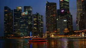 Barca turistica e Marina Bay Financial Center illuminata stock footage