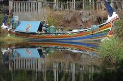 Barca variopinta completa con i rifornimenti in uno stagno con le riflessioni Fotografie Stock