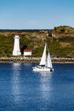 Barca a vela bianca che passa un faro bianco in acqua blu Immagini Stock Libere da Diritti