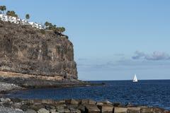 Barca a vela bianca sotto una scogliera Fotografia Stock