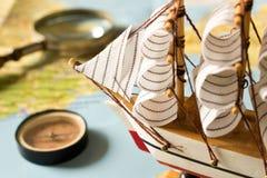 Barca a vela, bussola e lente d'ingrandimento di modello sul fondo della mappa Immagine Stock Libera da Diritti