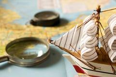 Barca a vela, bussola e lente d'ingrandimento di modello sul fondo della mappa Fotografie Stock
