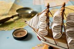 Barca a vela, bussola e lente d'ingrandimento di modello sul fondo della mappa Fotografia Stock