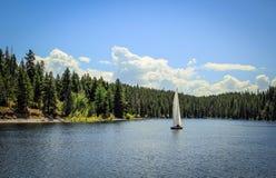 Barca a vela che galleggia lungo il lago Fotografia Stock