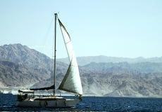 Barca a vela che naviga in rosso mare immagini stock libere da diritti