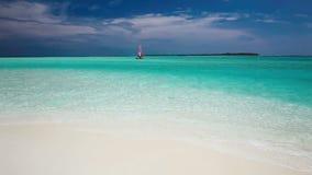 Barca a vela con la vela rossa su una spiaggia dell'isola tropicale video d archivio