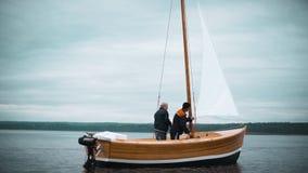 Barca a vela di legno con due uomini che provano a mettere albero video d archivio