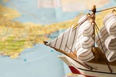 Barca a vela di modello sui precedenti della mappa concetto di corsa Immagine Stock