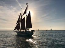 Barca a vela in mare aperto al tramonto Immagine Stock