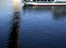 Barca a vela in mare con le riflessioni sulla superficie blu dell'acqua di estate Immagine Stock