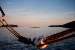 Barca a vela nel fondo con le corde al tramonto Fotografia Stock