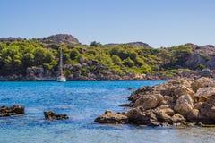 Barca a vela nella laguna blu del mare - baia di Ladiko, isola di Rodi, Grecia Fotografie Stock