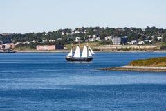 Barca a vela nera con le vele bianche Fotografia Stock