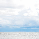 Barca a vela sola in mare, cielo nuvoloso ed acqua dell'argento Fotografie Stock Libere da Diritti