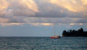 Barca a vela sopra le nuvole tristi al tramonto Immagine Stock Libera da Diritti