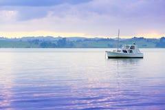Barca a vela su acqua con bello paesaggio ai precedenti Fotografia Stock