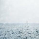 Barca a vela su Misty Blue Seas Fotografia Stock