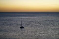 Barca a vela sull'oceano nel tramonto Fotografia Stock Libera da Diritti