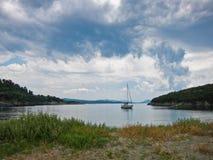 Barca a vela in una piccola baia sotto le nuvole scure a Sithonia Fotografia Stock