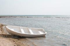 Barca vuota su una spiaggia abbandonata Fotografie Stock Libere da Diritti