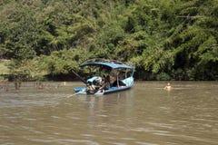 Barcaccia che lascia villaggio mentre i bambini sono nell'acqua immagini stock libere da diritti