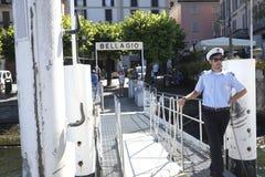 Barcaiolo che aspetta l'arrivo della barca al terminale a Bellagio sul lago Como Immagine Stock