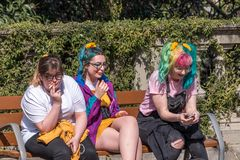 Barcelona, ​​Spain - March 12, 2019: Young girls with colored hair sit on the street stock image