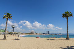 Barcelona beach panorama, Spain. Barcelona, Spain - May 16, 2014: Beautiful summer morning on Barceloneta beach. Image shows people sunbathing quietly and Royalty Free Stock Photo