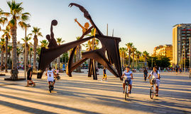 Barcelona Beach promenade. Tourists  along Barcelona promenade near Homage To Swim, Alfredo Lanz Sculpture, Barceloneta Beach  in the summer, Catalunya, Spain Royalty Free Stock Photo