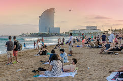 Barcelona beach with tourists at sunset. Barcelona beach with tourists enjoying the sunset and the sea royalty free stock photos