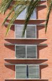 Four windows with jalousie on a brick red wall background with palm le royalty free stock photography