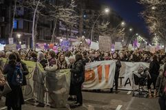 A large group of women of all ages is in the feminist protest on March 8 in an avenue of the city of Barcelona, Spain stock photos