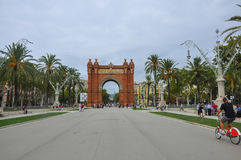 BARCELONA, CATALONIA SPAIN - SEPTEMBER 2016: Arc de Triomf with tourists, palm trees and red bicycle nearby. Horizontal view on Tr Royalty Free Stock Photography