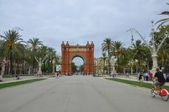 BARCELONA CATALONIA SPANIEN - SEPTEMBER 2016: Båge de Triomf med den närliggande turister, palmträd och röda cykeln Horisontalsik Royaltyfri Fotografi